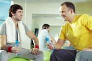 Two men communicating at gym while resting Stock Photos