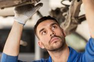 Mechanic man or smith repairing car at workshop Stock Photos
