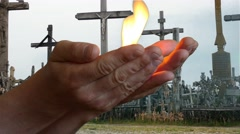 Man bringing fire burning in arms with Crosses background Stock Footage