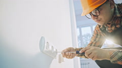 Electrician testing the current to a wall plug Stock Footage