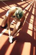 Young girl lacing up running boots at stadium Stock Photos
