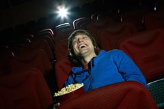 Young man laughing at comedy in cinema hall Stock Photos