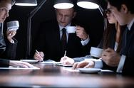 Four business people discussing their business late in the evening Stock Photos