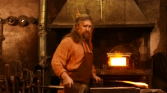Senior blacksmith forging the molten metal on the anvil in smithy Stock Footage