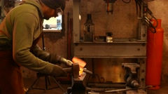 The blacksmith forging the molten metal on the anvil in smithy Arkistovideo