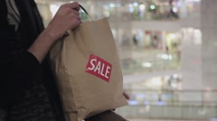 Male hands puts brown paper bag with red SALE sticker on it on handrail in Stock Footage