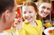 Close-up of a little girl feeding her father with spoon and smiling Stock Photos