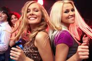 Two young blondes dancing against their friends Stock Photos