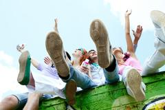 Four carefree teenage friends sitting on the wall and having fun Stock Photos