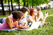 Four teenage friends lying on grass together Stock Photos