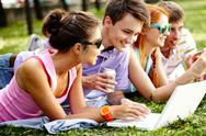 Four students lying on grass together and resting Stock Photos