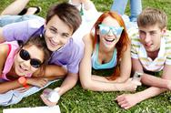 Four friends lying on grass together, looking at camera and smiling Stock Photos