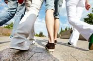 Legs of four friends walking together Stock Photos