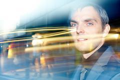 A businessman looking away through glass with flares Stock Photos