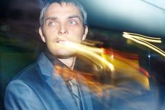 A businessman looking away among street illumination flares Stock Photos
