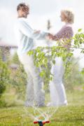 Playful couple through sprinkler splashes Kuvituskuvat