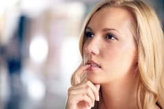 Face of a beautiful woman looking away in doubt Stock Photos