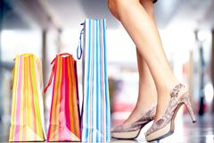 Three shopping bags at slim female legs in high-heeled shoes Stock Photos