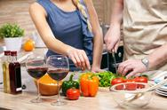 A table with products and a cooking couple by it Stock Photos