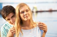 A young man embracing his girlfriend, looking at camera and smiling Stock Photos