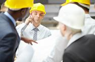 Young architect talking on the phone among his colleagues Stock Photos