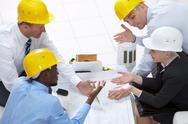 Four engineers meeting to make corrections of the project Stock Photos