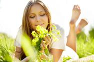 A beautiful girl lying on grass with flowers Stock Photos