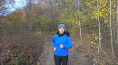 Woman  jogging cross country running on trail in forest. Training and exercis Stock Footage