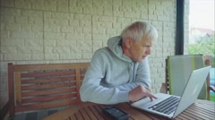 Senior man surfing on internet outside the house sitting on the porch Stock Footage