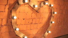 Wooden heart lantern standing against a red brick wall Stock Footage