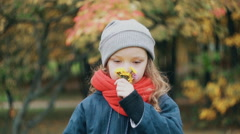 Funny little girl holding a small bouquet and enjoy the scent of wildflowers in Stock Footage