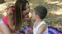 Mother and son bite of juicy apple from two sides Stock Footage