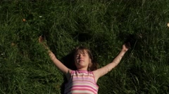 Child lays down to rest on green grass  Stock Footage