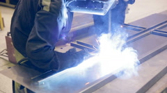 Two welders working, welding metal pieces together at a industrial factory Stock Footage