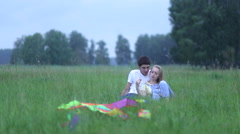 Young couple in love lying on the grass in the field, hugging and talking. Stock Footage