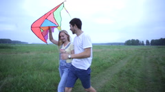 Young couple in love walking on summer field and hugging. The girl holding a kit Stock Footage