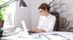 Female designer typing on laptop pick up phone refuse sitting at workplace Stock Footage