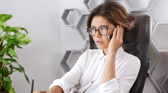 Nervous businesswoman talking on phone thinking refuse sitting in armchair Stock Footage
