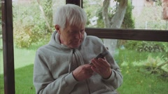 Senior man gray hair use a smartphone sitting on the veranda in the garden Stock Footage