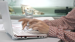 Female hands typing on the keyboard on the background of the aquarium Stock Footage
