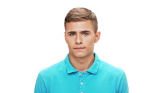 Displeased young man looking at camera over white background Slow motion Stock Footage