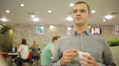 Young man drinking a coffee at the cafe. eating french fries Stock Footage