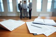 Office table with laptop and documents, three business people are in the backgro Stock Photos