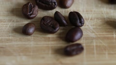 Rotating roasted coffee beans background concept on desk Stock Footage