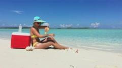 Woman in bikini apply cream on her skin on the beach in Exuma, Bahamas Stock Footage