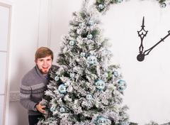 Happy young man and Christmas tree at home Stock Photos