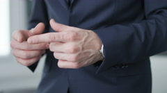 Businessman playing with his hands and checking hour on his watch Stock Footage
