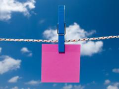Blank square of red paper suspended from a washing line. Stock Photos