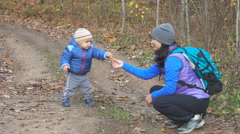 A mother feeds her little child in autumn forest on the trail. Stock Footage