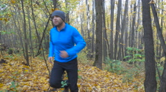 Man  jogging cross country running on trail in forest. Training and exercisin Stock Footage